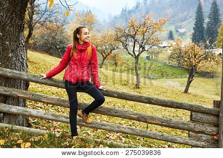 Portrait Of A Happy Woman Sits On A Rural Fence On A Hillside