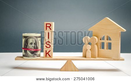 Wooden House And Cubes With The Word Risk And Family Stand On Scales. The Concept Of Risk, Loss Of R