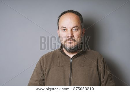 Middle Aged Man In His 40s With Short Dark Hair And Graying Beard Against Gray Wall With Copy Space