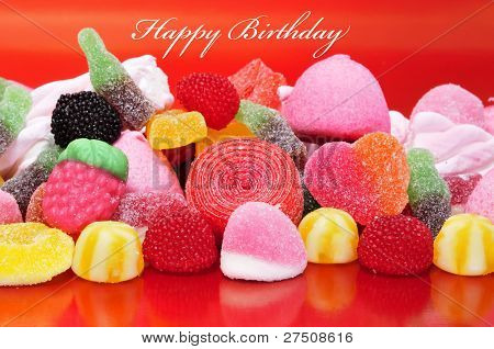happy birthday with a pile of candies on a red background