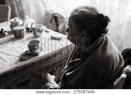 Black And White Image Of An Old Depressed Woman. An Elderly Lonely Woman Sits At A Table In The Kitc