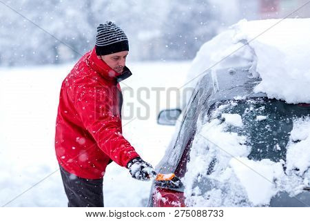 Cleaning Car From Snow. Young Men Cleaning Car Windshield From Snow And Ice After Snow Storm.