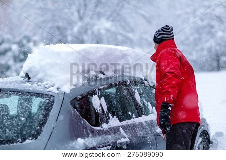 Young Man Is Cleaning Clean Off His Car Of Snow Cover By Brush. Snow Covered Car. Heavy Snow Cleanin