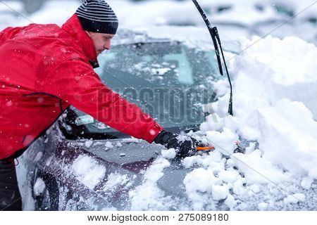 Winter Problems Of Car Drivers. Machine, Covered With Snow. A Man Brushing Snow From The Car. Young