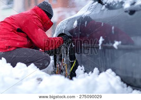 Snow Chains On The Wheels Of Car. Young Man Preparing Car For Travelling At Winter Day.