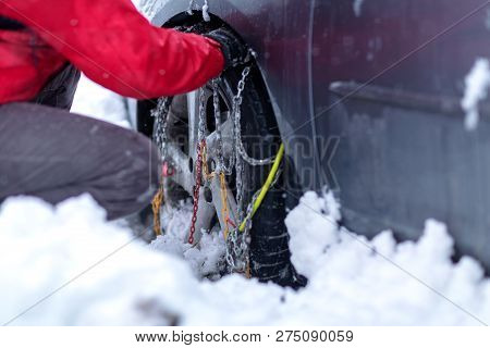 Young Man Preparing Car For Travelling At Winter Day. Snow Chains On The Wheels Of Car.