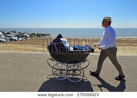 Felixstowe, Suffolk, England -  May 06, 2018: Man In Hat Pushing Vintage Pram Along Seafront Promena
