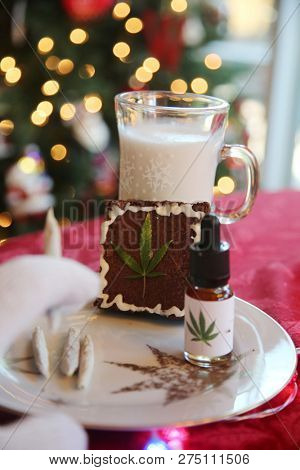 Christmas Marijuana Brownies. Marijuana Edible Brownies with milk for Santa Claus. Christmas Tree out of focus in background. Medical and Recreational Cannabis. gift for Santa Claus. Christmas Images.