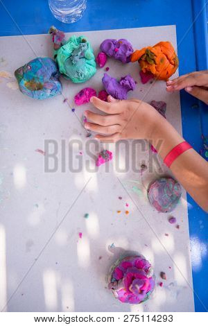 top view of kid hands Playing with Colorful Clay in outdoor Playground