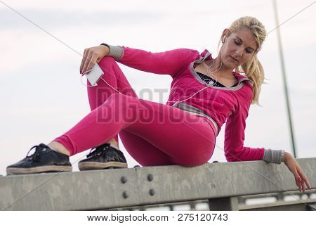 Attactive Trendy Blond Hair Woman In Pink Sports Clothing Is Sitting Outdoors And Using Phone.
