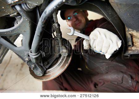 mechanic repairman at car break disk maintenance work by using spanner