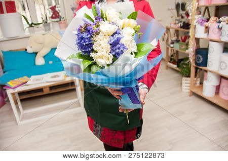 A Florist Holds A Large Bouquet Of White And Blue Flowers In A Florist Shop