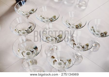 Martini Row On Table Party At Wedding Reception. Martini Drinks In Crystal Glasses At Alcohol Bar. C