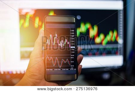 Businessman trading exchange board data on mobile screen / forex charts graph exchange on smart phone - Hand man and Stock market chart / Money forex Trade Graph Chart financial Concept