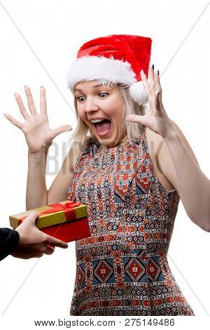 Image of joyful woman in Santa's cap and man's hands with gift