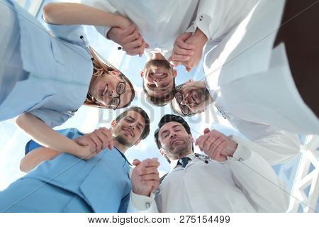 Medical staff standing in a circle at a meeting
