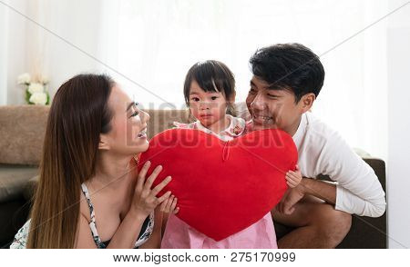 Happy Family Mother Father And Daughter Holding Heart Pillow At Home