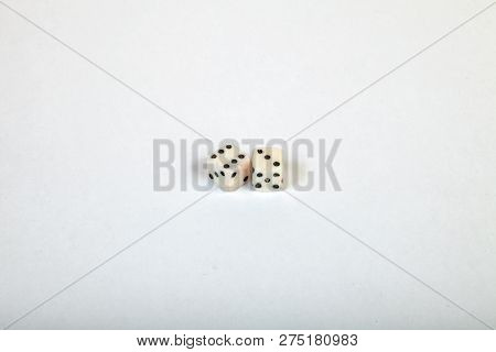 Two Very Small Dice Near Each Other On A Large White Isolated Background With The Numbers Six And Th