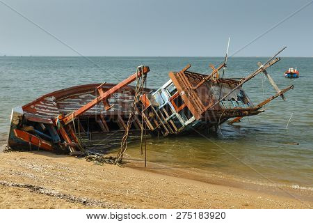 Fishing Boat Crashed Lies On Its Side Near The Shore, Old Shipwreck Or Abandoned Shipwreck