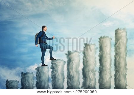 Confident Man Climb Up To The Top Of A Graph Made Of Clouds Over Blue Sky Background. No Limits Grow
