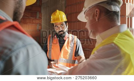 Supervisor Showing Building Plans To Workers In New House