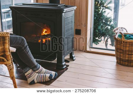 Cold fall or winter day. Woman resting by the stove. Closeup photo of human feet in warm woolen socks over fire place. Hygge concept of cozy winter weekend in cabin.