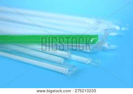 White And Green Plastic Drinking Straw On Blue Background