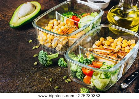 Healthy Meal Prep Containers With Chickpeas, Chicken, Tomatoes, Cucumbers, Avocados And Broccoli. To