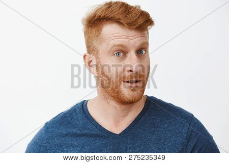 Headshot Of Intrigued Good-looking Ginger Male With Bristle In Blue T-shirt Turning At Camera With I