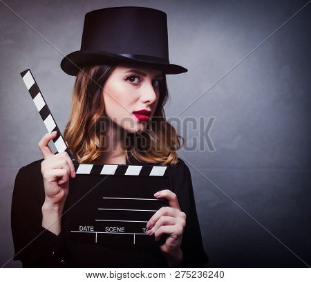 Style And Mystique Redhead Girl In Top Hat With Movie Clapperboard On Grey Background