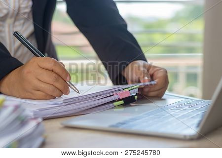 Hand Of Business Analyst Holding Pen Is Analyzing Graphs About Marketing In Office. Unfinished Paper