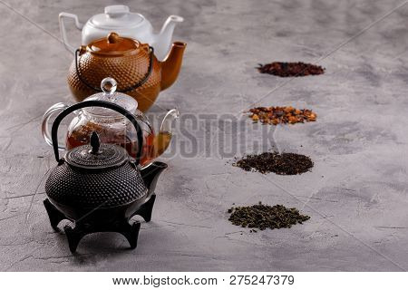 Tea card. Different in appearance teapots on a gray background, different types of tea. Tea still life. Concept. poster