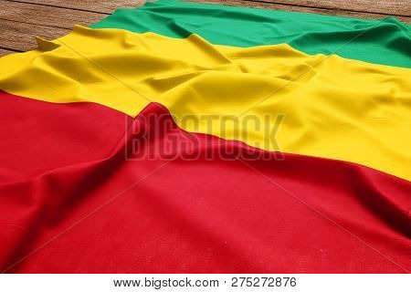 Flag Of Guinea On A Wooden Desk Background. Silk Guinean Flag Top View.
