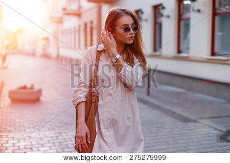 Fashionable Young Hipster Woman In Stylish Sunglasses In Trendy White Dress With A Fashionable Brown