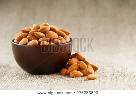 Almonds In A Wooden Cup On A Burlap Cloth Background.