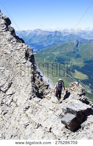 two mountain climbers on a narrow and exposed rock ridge on Eiger mountain in the Swiss Alps near Grindelwald poster