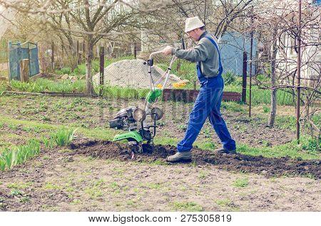 Man Working In The Spring Garden With Tiller Machine