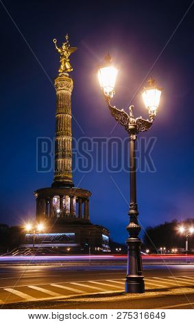 Illuminated Berlin Victory Column (Siegessaule) monument, a major tourist attraction of Berlin at night with street lamppost in foreground, Tiergarten, Berlin, Germany