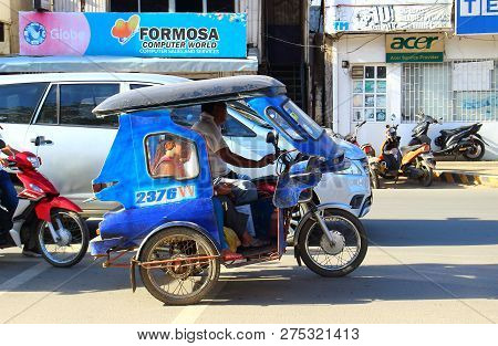 Palawan, Philippines - September 26, 2018: Tricycle Motorbike Taxi On City Street With Passengers. M