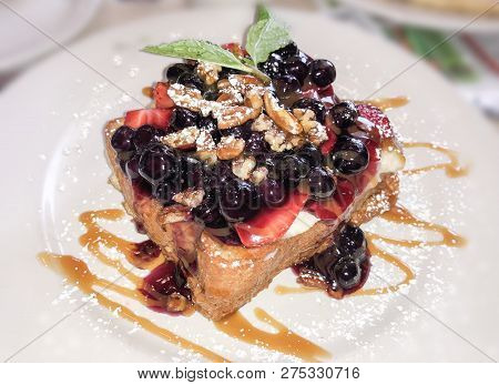 French toast. Breakfast of french toast with fresh berries and maple syrup. French toast with strawberries, berries, walnuts and dripping maple syrup and mint leaves on white plate. Love for a healthy desserts concept closeup. French toast on white table