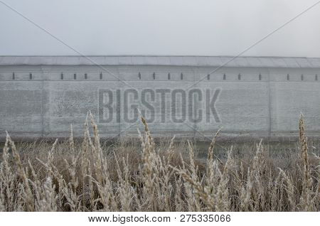 Wall Of The Fortress In The Fog At Sunrise With Blurred Grass In The Foreground. The Walls Of The Ru