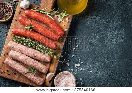 Assorted Fresh Sausages With Thyme, Rosemary, Olive Oil And Garlic On A Wooden Chopping Board On A D