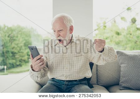 Portrait Of Mad Fury Old Man Wearing Checked Shirt Sitting On Divan Holding In Hand Phone Going Craz