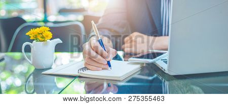 Business Woman Writing On A Notebook With A Pen In The Office.web Banner.