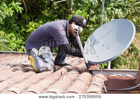 Technician Installing Satellite Dish And Television Antenna On Roof Top