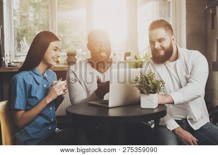A Company Of Young People Working For A Laptop. A Bearded Man With An African American And A Smiling
