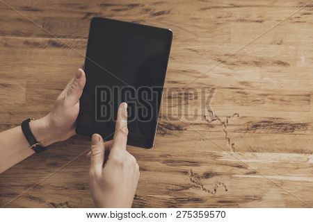 Top View Of Hands Holding Tablet Table Background. Using A Tablet To Access The Internet. Technology