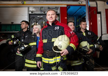 Image of four firemen and woman on background of fire truck
