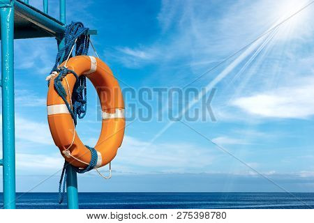 Orange And White Life Buoy With Ropes Hanging On A Lifeguard Chair With Sea, Blue Sky, Clouds And Su