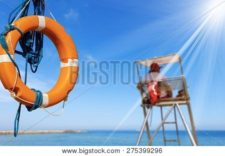 Orange And White Life Buoy With Ropes On A Background With Blue Sea, Lifeguard, Surveillance Tower,
